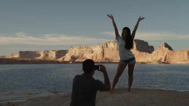 vídeos de stock e filmes b-roll de ws ds man photographing woman standing on rock near lake powell / utah, usa - lago powell