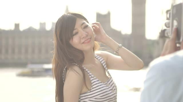 vídeos de stock, filmes e b-roll de man photographing woman with big ben in background - sem manga