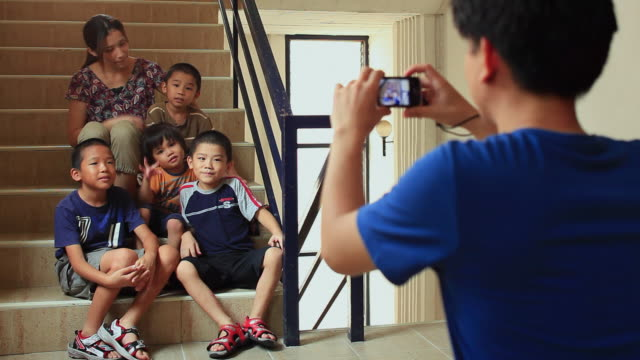 ms man photographing woman with four sons (8-9, 6-7,4-5, 2-3) sitting on stairs / watthana, bangkok, thailand - photographing stock videos & royalty-free footage