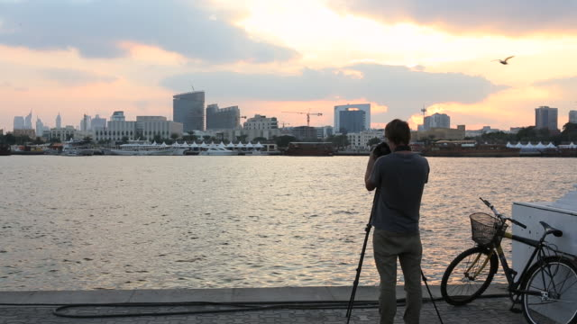 man photographs on dubai creek, financial district behind - camera photographic equipment stock videos and b-roll footage