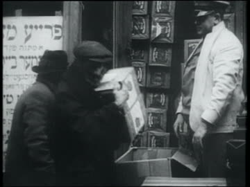 b/w 1932 man picking up 2 boxes of free matzos from store / lower east side, nyc - judaism stock videos & royalty-free footage
