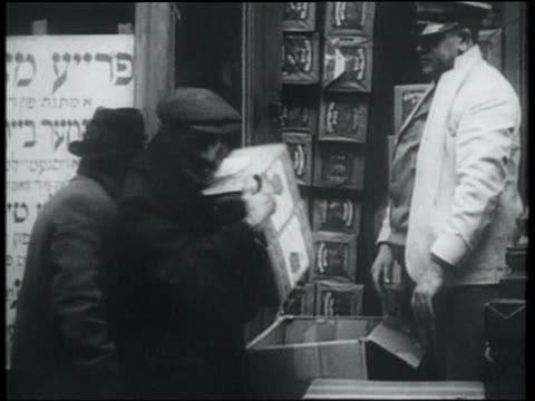 vídeos y material grabado en eventos de stock de b/w 1932 man picking up 2 boxes of free matzos from store / lower east side, nyc - 1930
