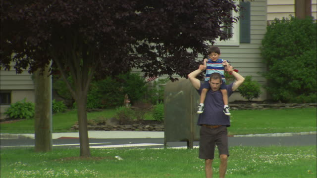 MS Man picking up boy, putting boy on his shoulders, and carrying him around suburban park/ Fanwood, New Jersey