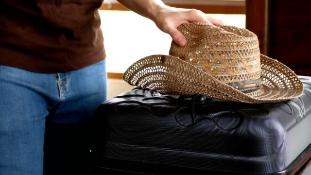 man picking up straw hat and carrying travel luggage out of bedroom for traveling - straw hat stock videos and b-roll footage