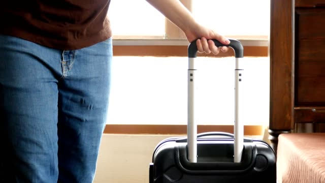man picking up straw hat and carrying travel luggage out of bedroom for traveling