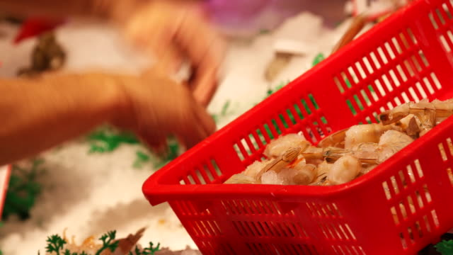 a man picks pieces of shrimp out of a seafood display case and tosses them into a basket in seattle washington on december 30 2018 - präsentation hinter glas stock-videos und b-roll-filmmaterial
