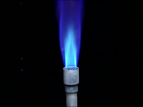 a man picks up a burning bunsen burner and ignites a substance on a stone slab. - bunsen burner stock videos & royalty-free footage