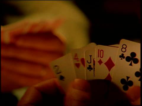 vidéos et rushes de man picks up jacks for his hand in poker game - poker