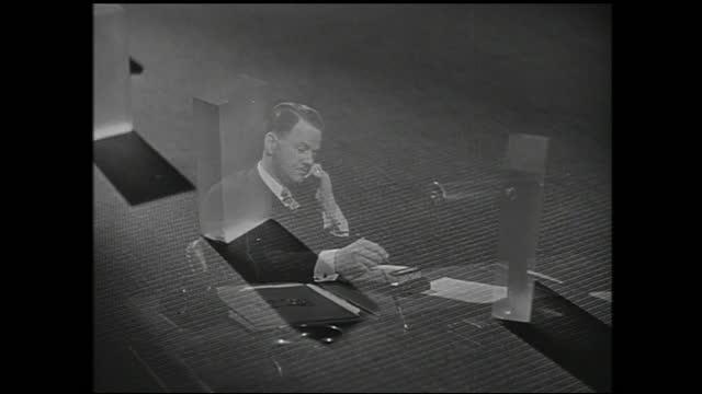 man picks up telephone behind office desk and talks while smiling; clear blocks rotate in superimposed image - 1940 1949 bildbanksvideor och videomaterial från bakom kulisserna