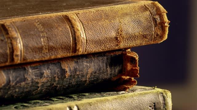 vídeos de stock e filmes b-roll de man piles up old leather-covered books - capa de livro