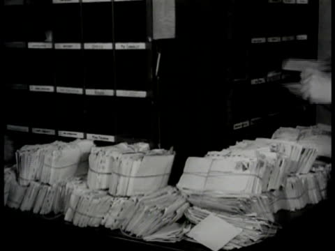 man piling mailbags. mail room workers unloading bags of letters. cutting open bundles of letters. mail sorter opener. vs men putting letters into... - anno 1947 video stock e b–roll