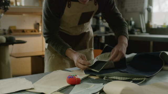 man pinning fabric in workshop / provo, utah, united states - provo video stock e b–roll