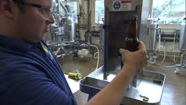 a man places a beer bottle into a chute and seals a cap on it. - beer cap stock videos & royalty-free footage