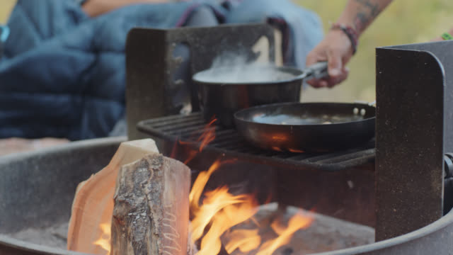 CU. Man places cooking pot and skillet on campfire grill.