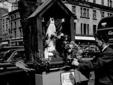 a man places flowers onto a street shrine in dublin - catholicism stock videos and b-roll footage
