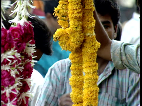 Man places garland of marigolds in shopper's bag Ahmedabad