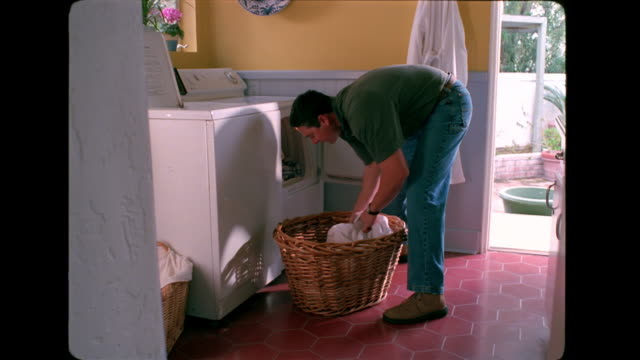 a man places laundry from a basket into the dryer. - wäschekorb stock-videos und b-roll-filmmaterial