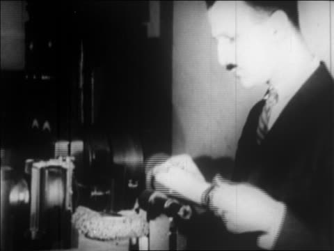 vidéos et rushes de man places photograph on cylinder onto light scanner to send photo by wire / newsreel - 1924