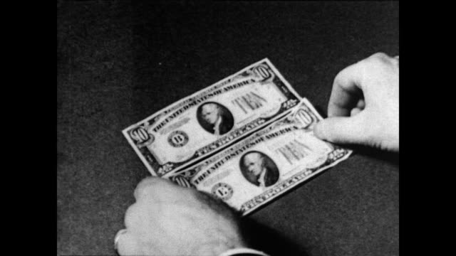 / man places two ten dollar bills next to each other / folds one in half and compares the portraits and markings to detect the counterfeit one... - banconota da 10 dollari statunitensi video stock e b–roll