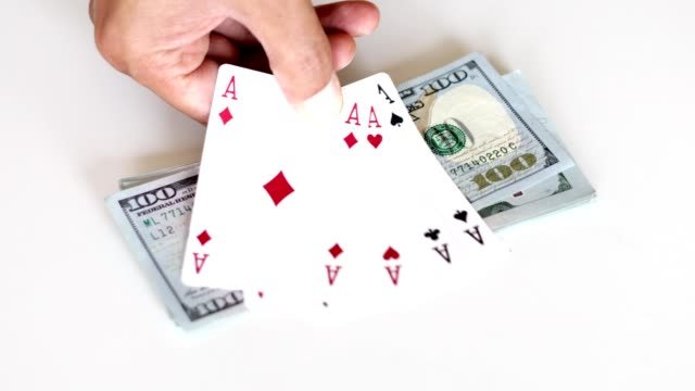 man placing a winning hand of cards on money. four aces - hand of cards stock videos & royalty-free footage