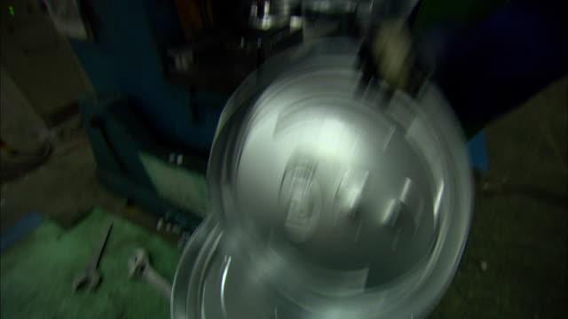 MS TD TU Man placing flat metal disk inside large machine at factory at Himin Solar Energy Group, Dezhou, Shandong, China