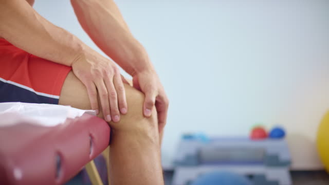 slo mo man placing hands on his knee because of the pain - massage table stock videos & royalty-free footage