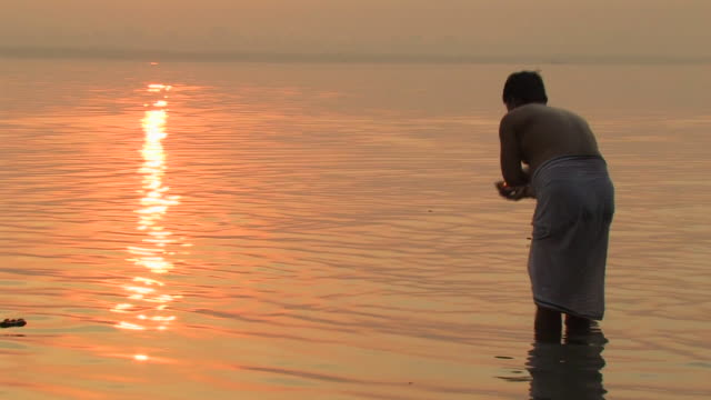 ms, man placing hindu votive candle (diya) onto ganges river at sunrise, rear view, varanasi, uttar pradesh, india - ceremony stock videos & royalty-free footage