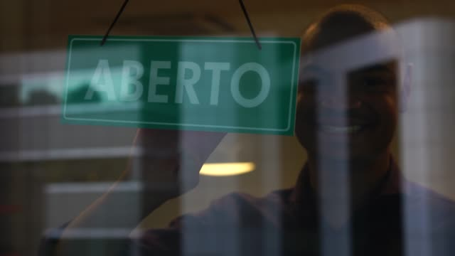 man placing open sign (in portuguese) on store - store sign stock videos & royalty-free footage