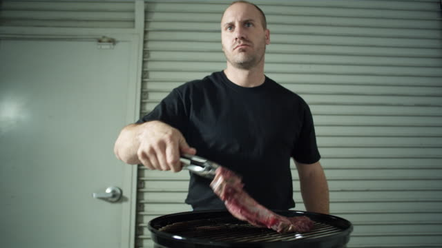 MS R/F, Man placing steak on barbecue in front of garage door, Los Angeles, California, USA