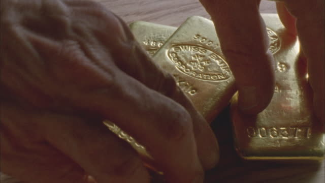 CU, Man placing three gold ingots on table, close-up of hands