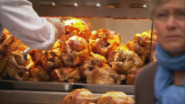 cu man placing whole roasted chickens into display cabinet at butcher shop / paris, france - display cabinet stock videos & royalty-free footage