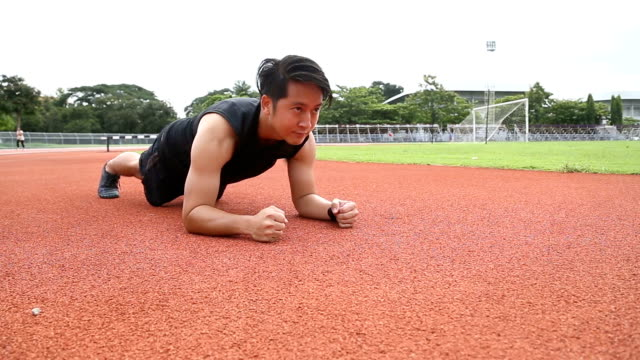 man planks exercises in track and field - low section stock videos & royalty-free footage