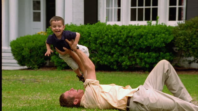 A man playfully lifts his son over his head as he lies in the grass.
