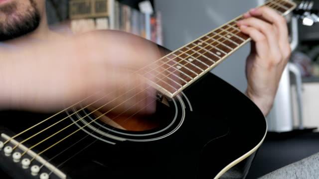 uomo che suona una chitarra acustica nero - compositore video stock e b–roll