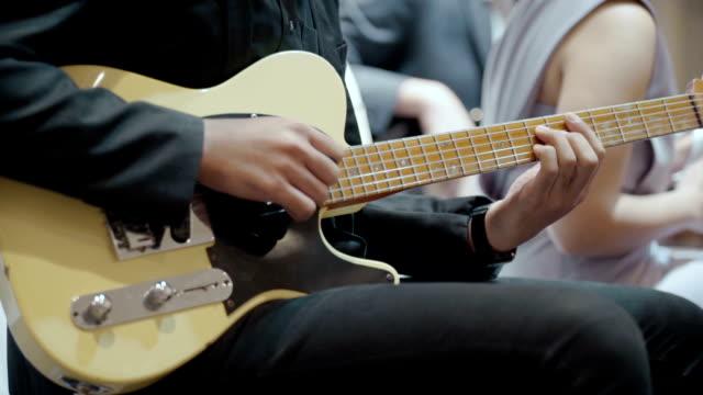 vídeos de stock, filmes e b-roll de homem tocando uma guitarra em um show de festa - guitarist