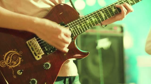 CU: Man een gitaarspelen op een rockconcert