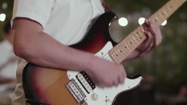 CU: Mann spielt eine Gitarre In der Partei in der Nacht