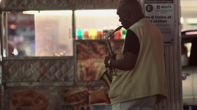A man playing a saxophone a vendor cart is behind
