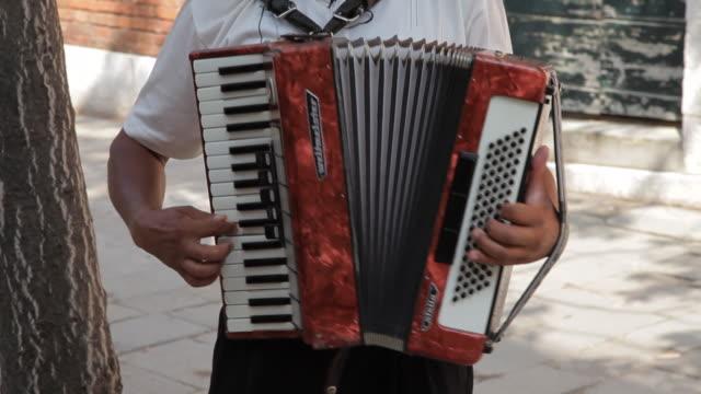 vídeos y material grabado en eventos de stock de mh tu man playing accordion on sidewalk / venice, italy - acordeonista