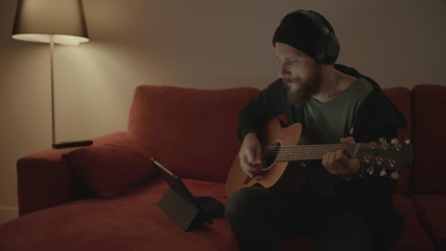 mann spielt akustikgitarre zu hause, aufnahme auf tablet - zuhören stock-videos und b-roll-filmmaterial