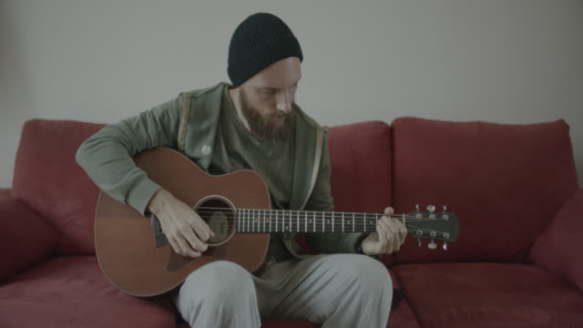 man playing acoustic guitar at home, recording on tablet - strumento musicale video stock e b–roll