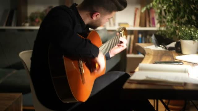 自宅でアコースティックギターを弾く男 - hobbies点の映像素材/bロール