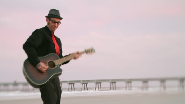 ms selective focus td man playing acoustic guitar on beach / jacksonville, florida, usa - hemd und krawatte stock-videos und b-roll-filmmaterial