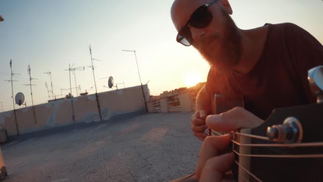 uomo che suona la chitarra acustica sulla terrazza durante il blocco covid-19 - balcone video stock e b–roll