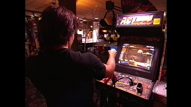 man playing action hero in video arcade. - 2000s style stock videos & royalty-free footage