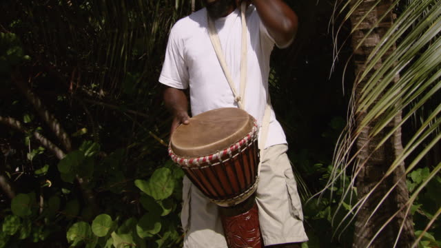 vidéos et rushes de ms tu man playing african drum on the beach / brightown, barbados - un seul homme d'âge moyen