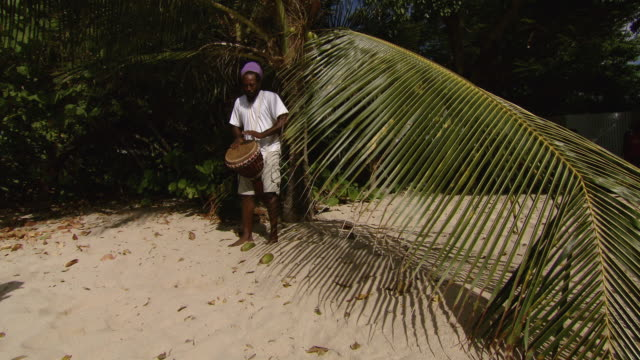ms man playing african drum on the beach / brightown, barbados - one mid adult man only stock videos & royalty-free footage