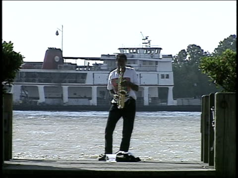 man playing alto sax by new orleans river - alto saxophone stock videos and b-roll footage