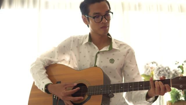 Homme qui joue une guitare acoustique à la maison