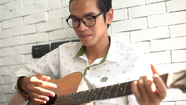 man playing an acoustic guitar at home - plucking an instrument stock videos and b-roll footage